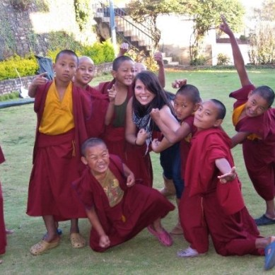 Young monks playing with volunteer