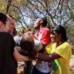 Students and volunteers doing trust fall exercise in Zimbabwe