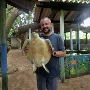 Justin holding a green sea turtle named Rosie