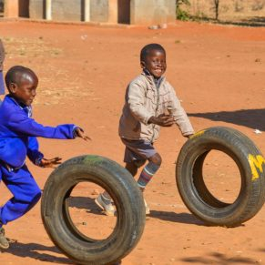 Two young boys racing while rolling tires