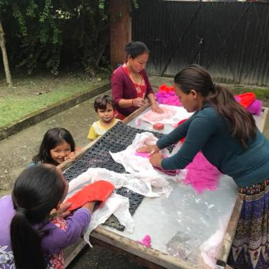 Women and children making crafts in Nepal