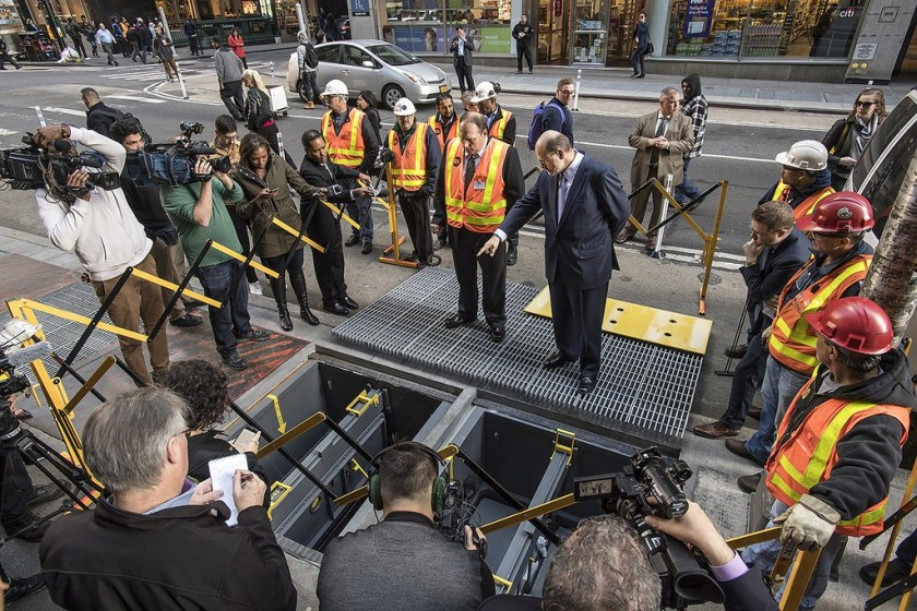 Photo of MTA Chaireman and press examining subway grating flood prevention devices
