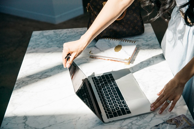 Woman Viewing Laptop On Marble Table