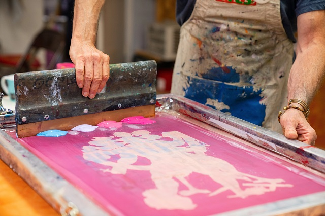 Person Screenprinting A Design With Multiple Paint Colors