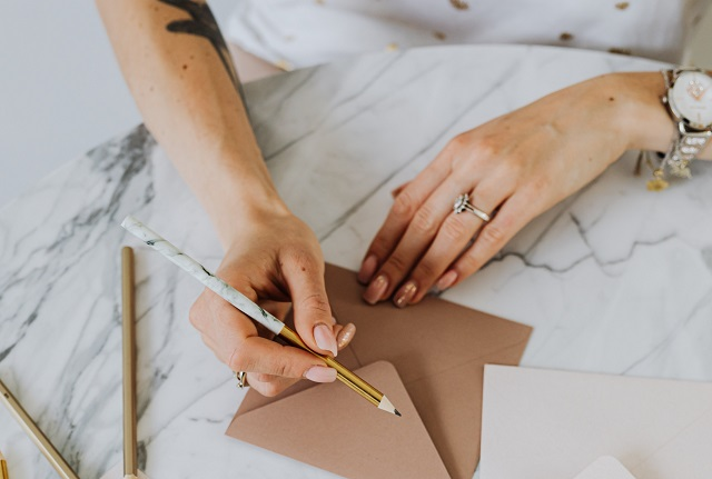 Woman writing letters on marble table