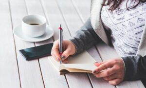 Woman taking notes on a wooden table