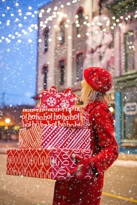 Woman on snowy street holding holiday presents