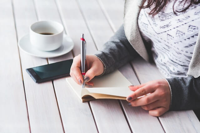Woman writing in a journal with a cup of coffee