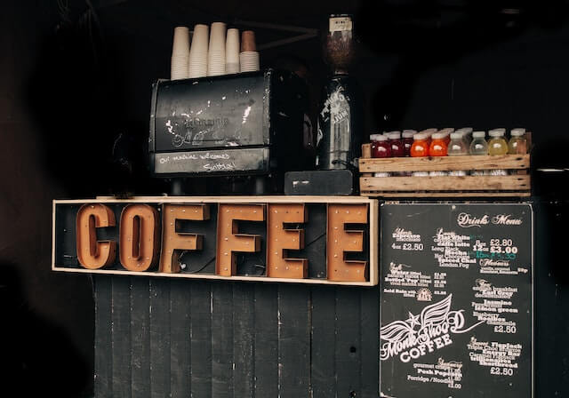 "Small beverage stand with large signage reading ""coffee"""