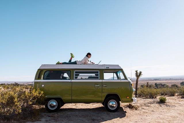 Lizzy VanPatten on a green camper van in the desert