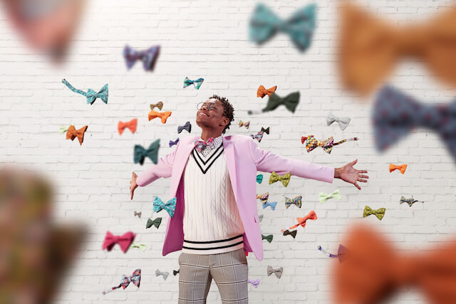 Moziah Bridges with arms out surrounded by falling bow ties