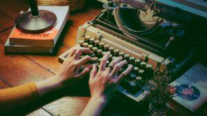 Person typing on old typewriter