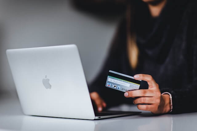 Person at computer holding a credit card
