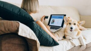 Woman making online payment with corgi resting nearby
