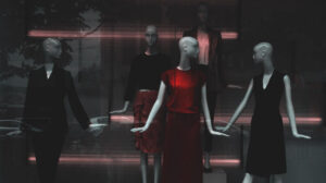 Red dress on display around black dresses