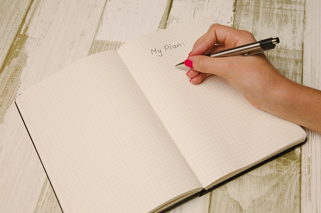 Woman Writing Outline In Journal