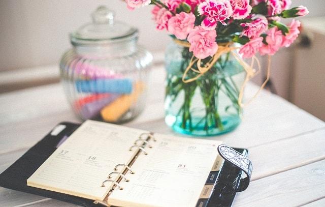 Open Planner On A Desk Near Vase Of Flowers