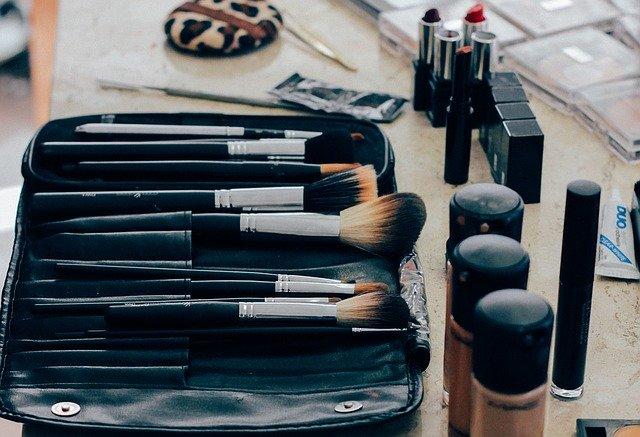 Makeup Brushes And Makeup Scattered On Desk