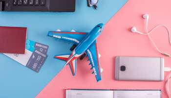 Plane, air tickets, passport, notebook and phone with headphones on pastel background. The view from the top. The concept of planning and preparing for the travel