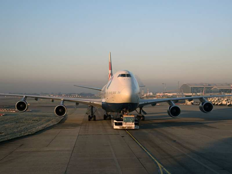 Passenger jet being moved using an aircraft tractor at Heathrow London Airport
