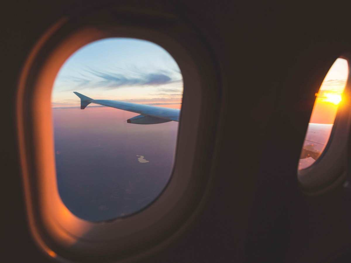 Sunset aerial view through airplane window over wings. Flying at sunset and looking out of the window and enjoying the panoramic view. Travel and transportation concepts