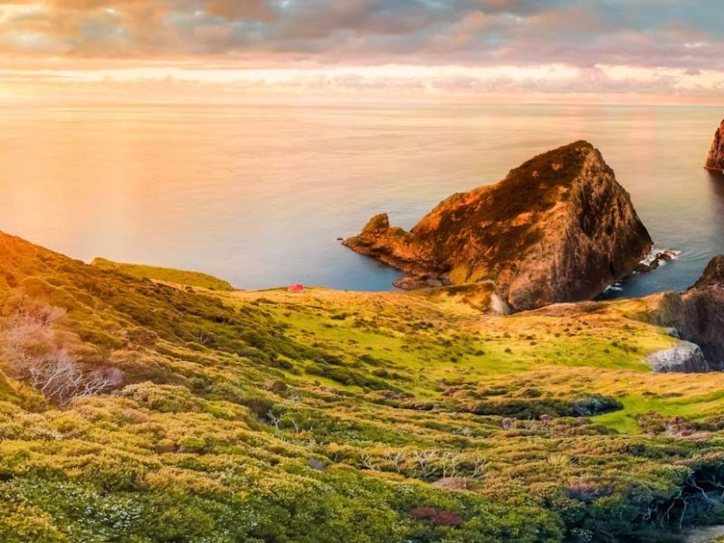 Scenic panorama of Cape Brett lighthouse on the coast of New Zealand during sunset. Located in Bay of Islands, popular tourist destination for its natural beauty.