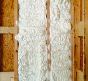 Close-up of spray foam applied between studs.