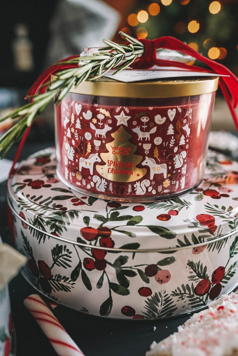 Yankee Candle christmas candle on top of a tin of christmas cookies tied with velvet ribbon as a gift
