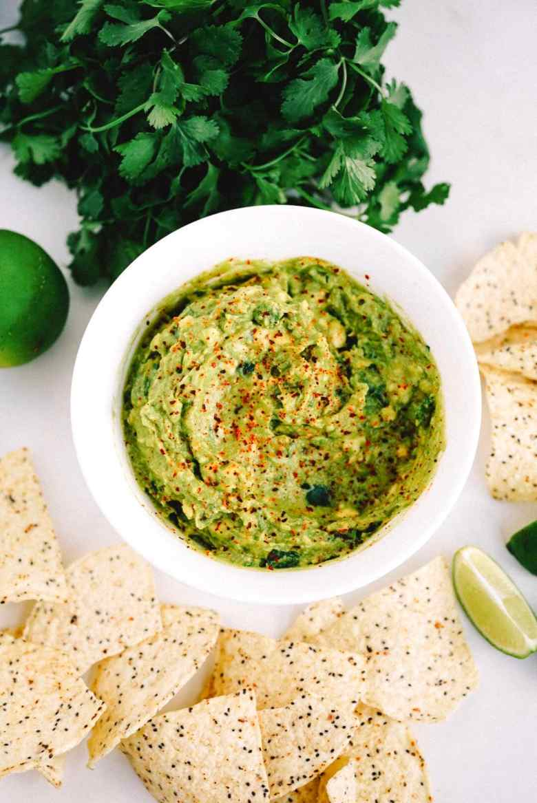 homemade guacamole in white bowl on white marble counter