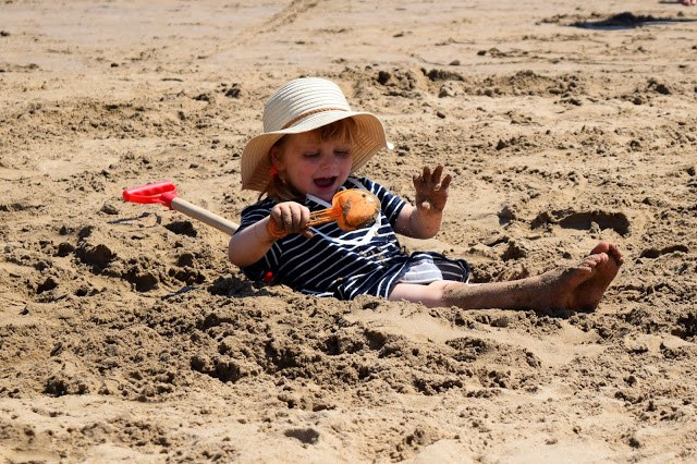 toddler covering herself with sand