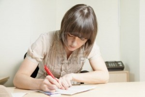 12835677-young-brunette-woman-writing-on-paper-sheet-at-office-desk