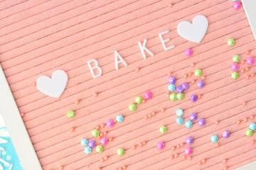 """Ein rosa Schild mit der Aufschrift """"Bake""""."""