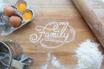 """Auf einer Arbeitsplatt steht das Wort """"Family"""" mit Mehl geschrieben."""
