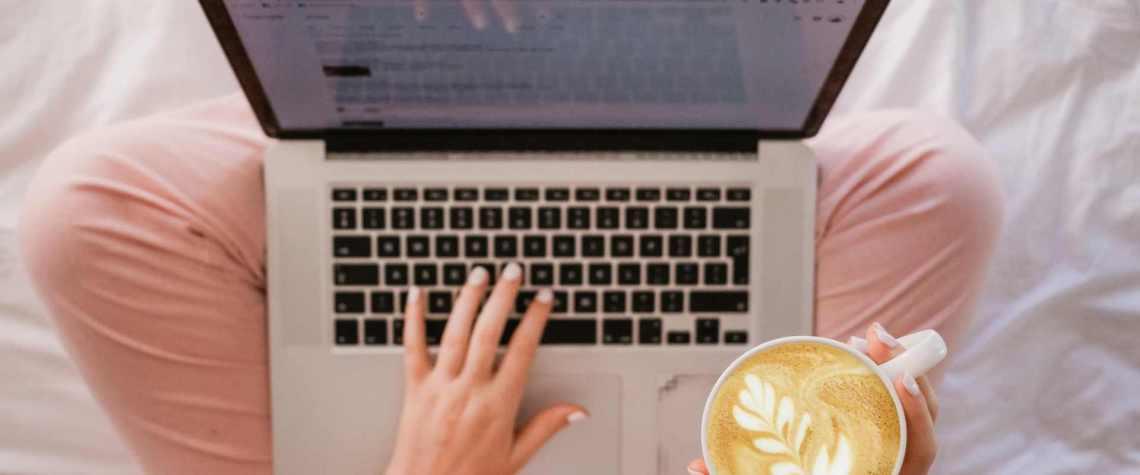 Frau tippt auf Laptop mit Cappuccino in der Hand