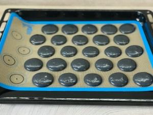 Schwarze Macarons auf einem Backblech