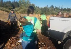 firewood volunteer with baby in backpack