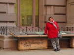 Tricia Hill posing in front of the United States Bankruptcy Court building in New York City.
