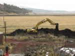 A Caterpillar excavator cleaning an irrigation canal on the Running Y Ranch.