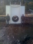 Two Walker Brothers employees stand by a large headgate that's about to planted in a canal at the Running Y Ranch.