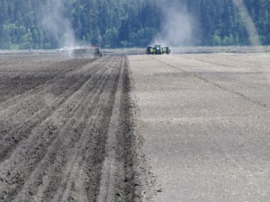 Two tractors and potato planters planting chipping potatoes at the Running Y Ranch.