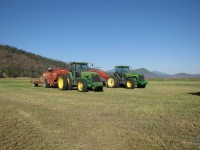 Two large hay bailers parked in a cut alfalfa field at the Running Y Ranch, Klamath Falls, OR.