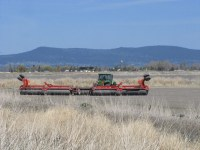 A field is being rolled by Walker Brothers with the town of Tulelake, CA, in the background.