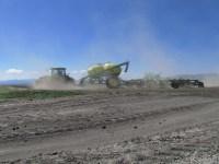 A John Deere tractor pulls grain planting equipment outside of Tule Lake, CA.