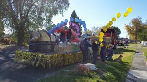 Gold Dust and Walker Brothers' employees tie balloons to a string to build a balloon rainbow for the 77th Annual Potato Festival parade in Merrill, Oregon.