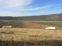 Two spud trucks drive to the Elk Field to join the day's potato harvest on the Running Y Ranch near Klamath Falls, OR.