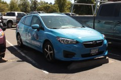 A blue Subaru wrapped with Make-A-Wish logos.