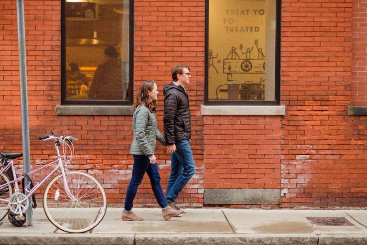 Couple in coats walk by a brick wall during a winter engagement session in Somerville, MA