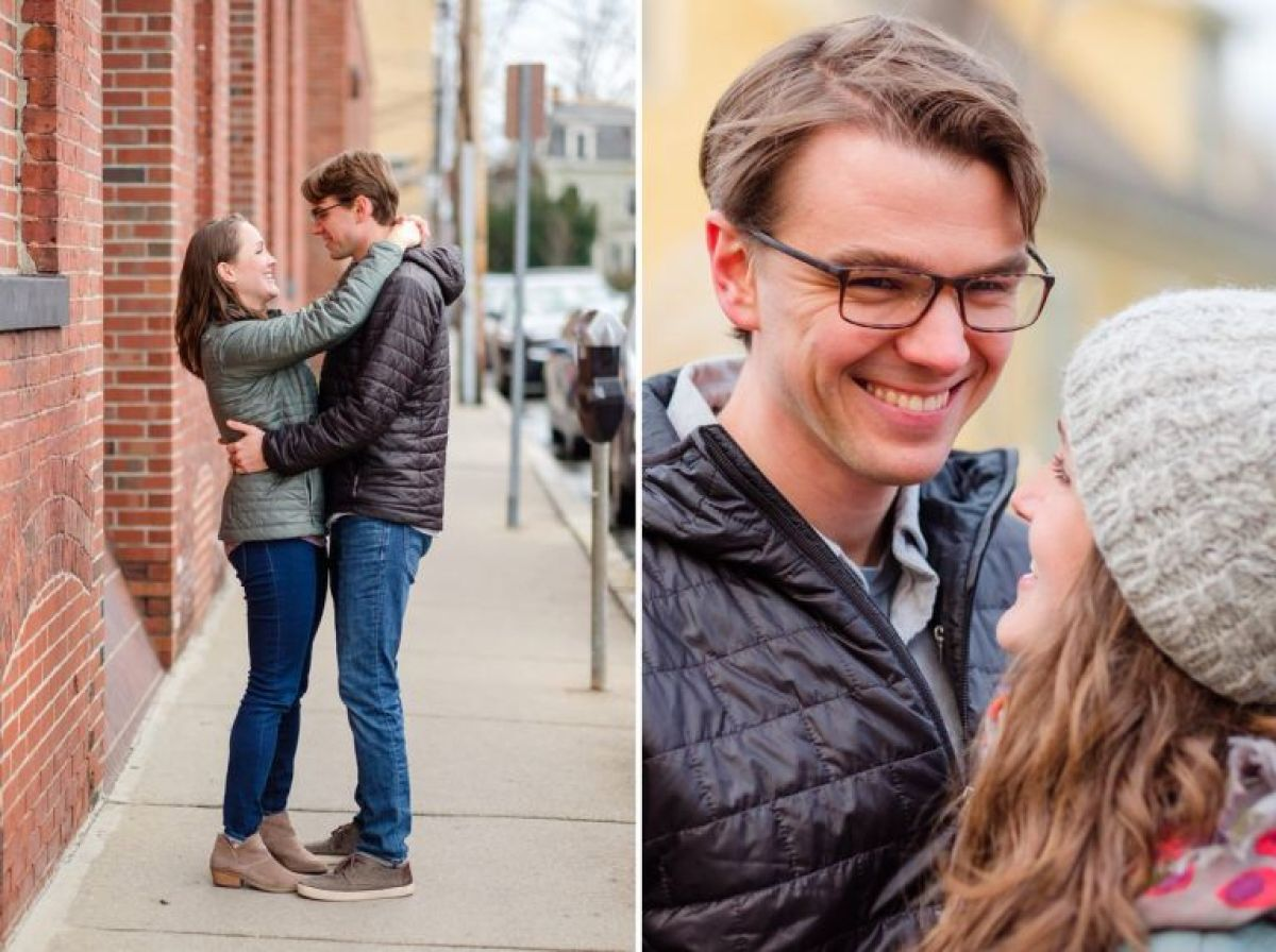Couple in coats dance by a brick wall during a winter engagement session in Somerville, MA