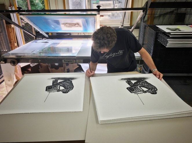 Nick Walker signing the prints