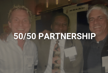 """The words """"50/50 Partnership"""" are across the image in white. Three men are joined at the shoulders, smiling for the photo. They are dressed in business casual suits and have name tags on their right side chest plate."""